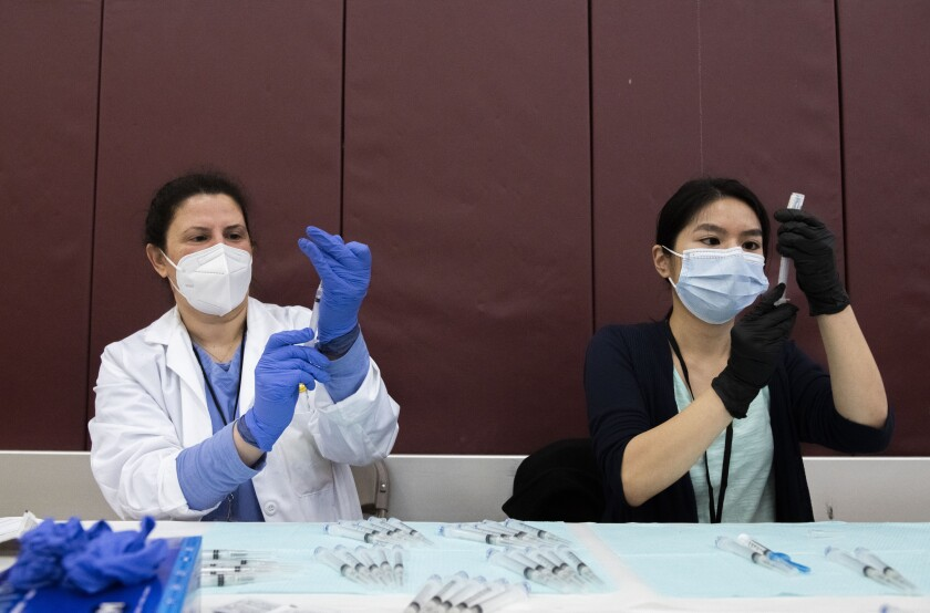 Pharmacists prepare syringes with COVID-19 vaccine.