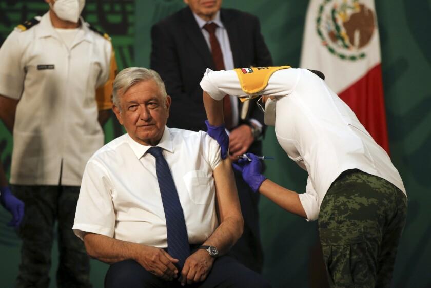 El presidente mexicano Andrés Manuel López Obrador recibe una inyección de la vacuna AstraZeneca