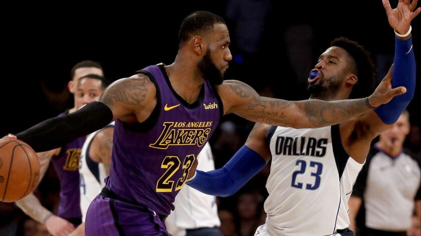 Lakers forward LeBron James parries with Dallas Mavericks guard Wesley Matthews in the fourth quarter on Friday at Staples Center.