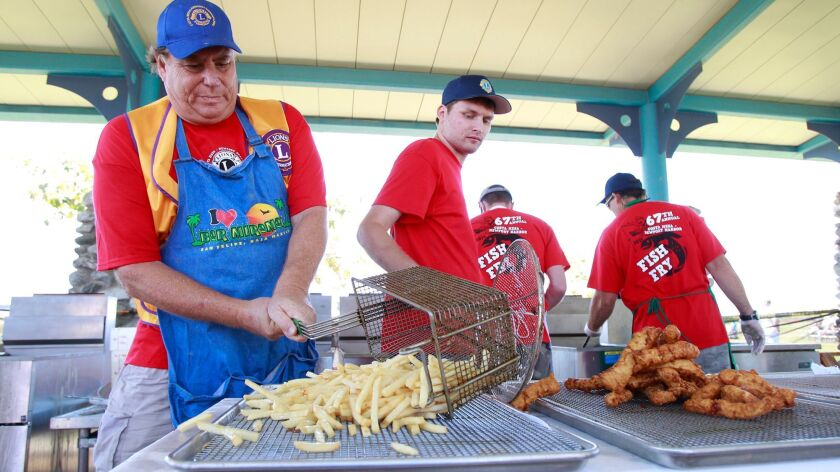 Longtime frier Rick Blake, left, dumps a fresh batch of french fries as fellow cook Vincent Williams