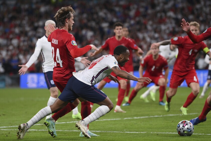 England's Raheem Sterling, left, is fouled by Denmark's Mathias Jensen and a penalty is awarded during the Euro 2020 soccer semifinal match between England and Denmark at Wembley stadium in London, Wednesday, July 7, 2021. (Laurence Griffiths/Pool Photo via AP)