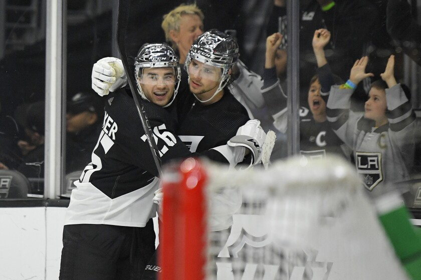 Kings center Adrian Kempe, right, celebrates his overtime goal with defenseman Sean Walker.