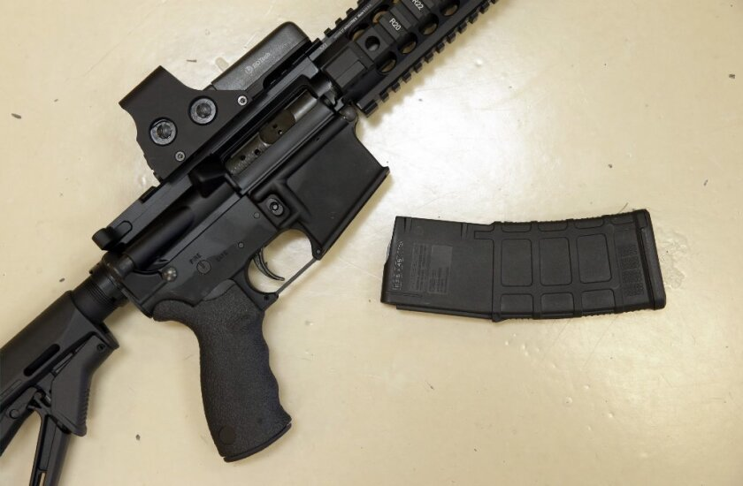 In this Oct. 3, 2013, file photo, a custom-made semi-automatic hunting rifle with a high-capacity detachable magazine is displayed at TDS Guns in Rocklin, Calif.