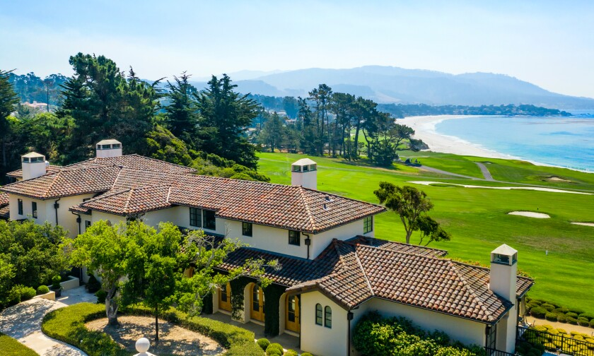 A mansion surrounded by trees that overlooks a golf course and the ocean.