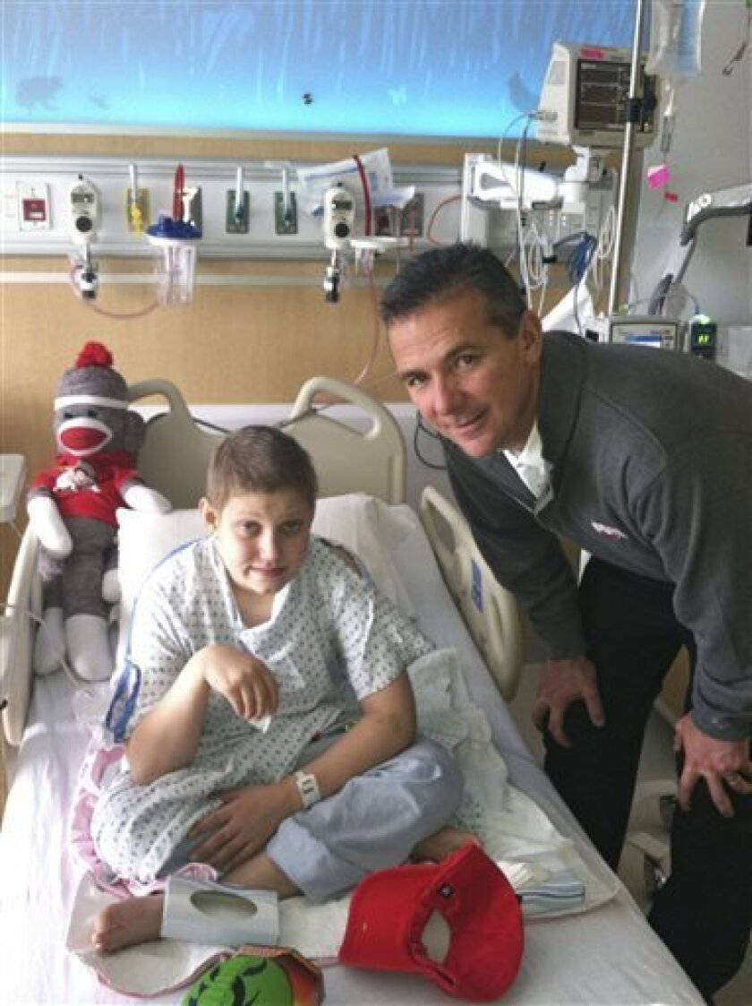 In this December 2012 photo provided by the Reed family, Ohio State football fan Grant Reed, left, poses with Ohio State football coach Urban Meyer at Nationwide Children's Hospital in Columbus, Ohio. When Grant, now 12, was diagnosed with cancer 14 months ago, he chose to name his disease Michigan. He wanted to beat it. And he did. Grant was released from the hospital on Friday, July 5, 2013, after a final chemotherapy session. (AP Photo/Reed Family)
