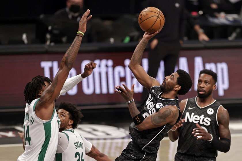 Brooklyn Nets guard Kyrie Irving shoots over Boston Celtics center Robert Williams III during the first half of an NBA basketball game, Thursday, March 11, 2021, in New York. (AP Photo/Adam Hunger)