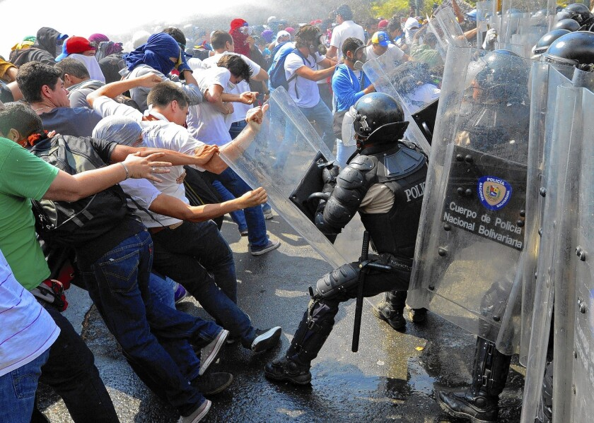 Venezuelan students demonstrating against the government battle riot police in Caracas, the capital.