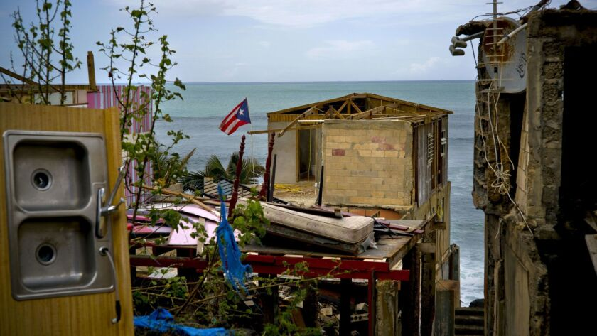 FILE - In this Oct. 5, 2017 file photo, a Puerto Rican national flag is mounted on debris of a damag