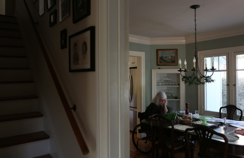 """Missy reads on her iPad in the dining room of her home.  """"I live in a walking neighborhood,"""" Missy says, """"and there are lots of people walking their dogs or just walking around, and, it seems absolutely just amazing to me and I, I don't think I appreciated that enough."""""""