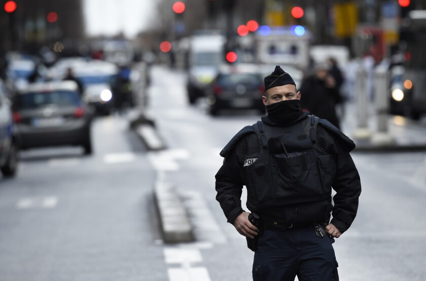 A French police officer stands at the Boulevard de Barbes in north Paris after a man armed with a knife and wearing what appeared to be an explosives vest was fatally shot at a police station.