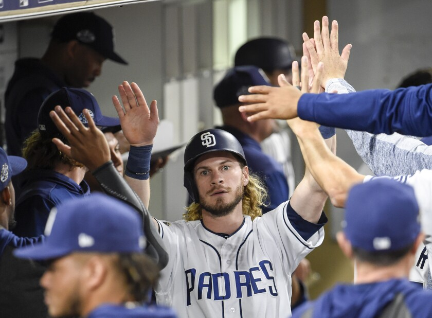 Travis Jankowski is congratulated in the Padres dugout after scoring during the seventh inning of Tuesday's game against the Chicago Cubs at Petco Park.