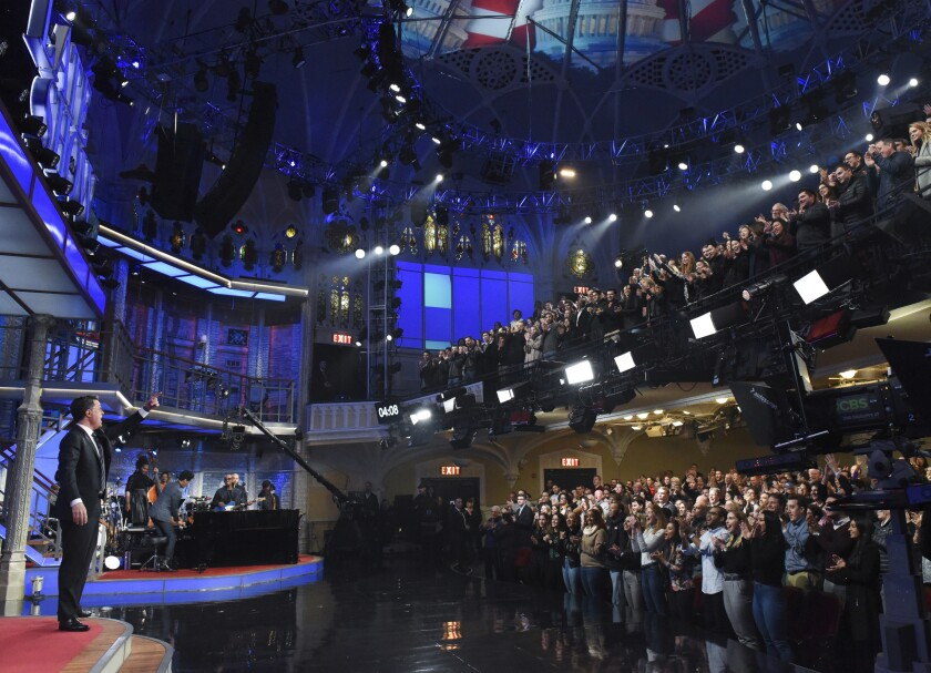 "This Feb. 4, 2020 image released by CBS shows host Stephen Colbert, left, greeting the audience during a taping of ""The Late Show with Stephen Colbert"" in New York. The show, along with other New York-based late night talk shows ""The Tonight Show Starring Jimmy Fallon"" and ""The Daily Show with Trevor Noah"" will tape their shows without studio audiences due to the new coronavirus. For most people, the new coronavirus causes only mild or moderate symptoms. For some it can cause more severe illness. (Scott Kowalchyk/CBS via AP)"