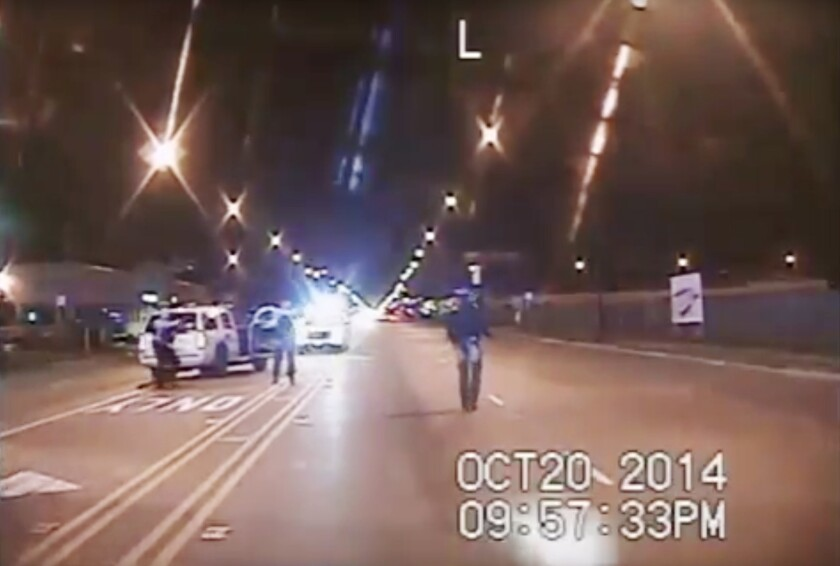 Image from dash-cam video prior to the shooting of Laquan McDonald, seen on the right walking in the street.