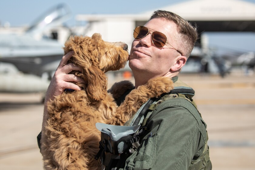 Lt. Col. Anthony Koehl picks up his 11 month old puppy Apollo for the first time