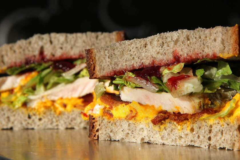 A turkey sandwich made with buckwheat bread, kabosha squash whipped with creme fraiche, applewood smoked bacon, hot carved turkey, romaine, and cranberry chutney prepared at Mendocino Farms in West Hollywood. Recipe.