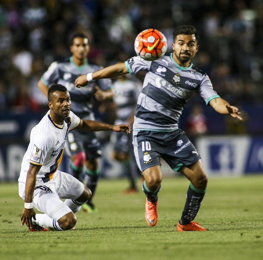 Santos Laguna midfielder Bryan Rabello, right, moves the ball away from Los Angeles Galaxy defender Ashley Cole during the first half of a CONCACAF Champions League soccer quarterfinal in Carson, Calif., Wednesday, Feb. 24, 2016. (AP Photo/Ringo H.W. Chiu)