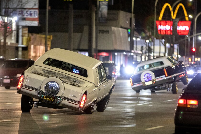 Low riders show off their capabilities while cruising Van Nuys Boulevard