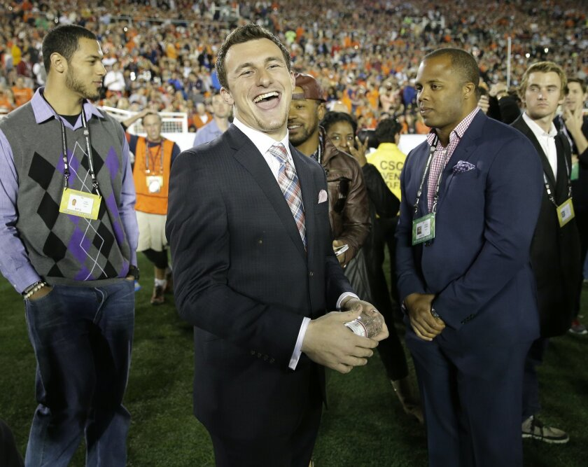Texas A&M quarterback Johnny Manziel smiles from the sidelines during the first half of the NCAA BCS National Championship college football game between Auburn and Florida State Monday, Jan. 6, 2014, in Pasadena, Calif. (AP Photo/David J. Phillip)