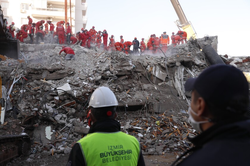 A goup of rescuers works amid the rubble of a building in Izmir, Turkey.