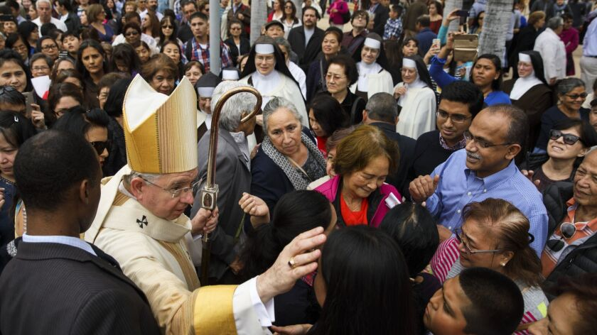 Los Angeles Archbishop José H. Gomez is surrounded by parishioners after the door closing ceremony m