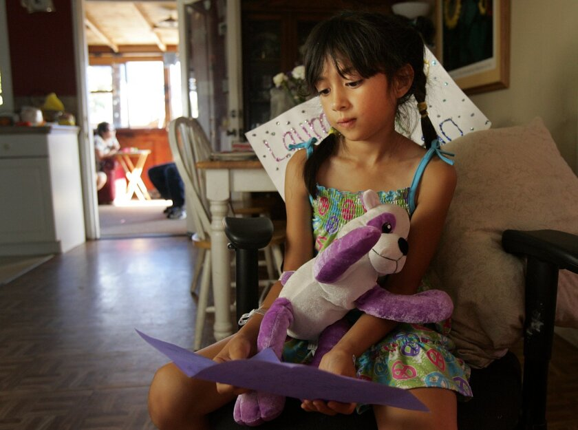 Laura Castelo, 7, shot and wounded over weekend in front of her Emerald Hills home, holds a get well card from a classmate after being released from the hospital on Tuesday, July 12, 2011.