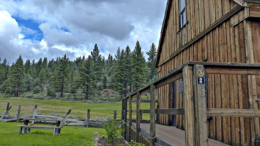 MARKLEEVILLE, CA - The old log jail in Markleeville, with the surrounding meadows and Sierras at the
