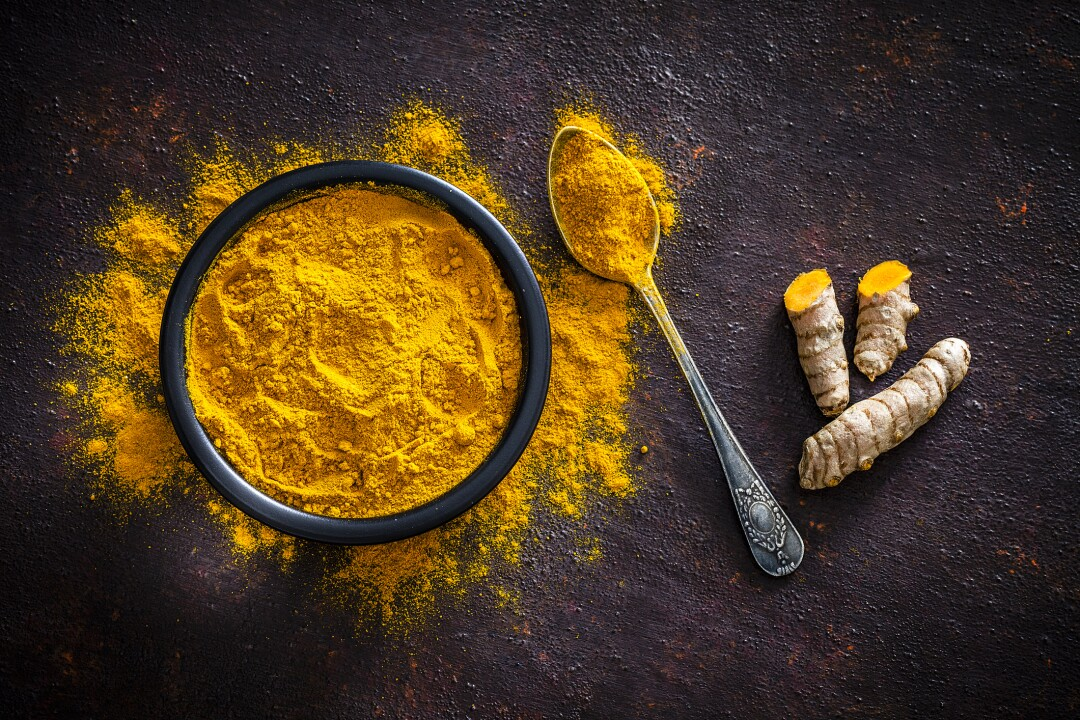 Spices: Turmeric roots and powder shot from above