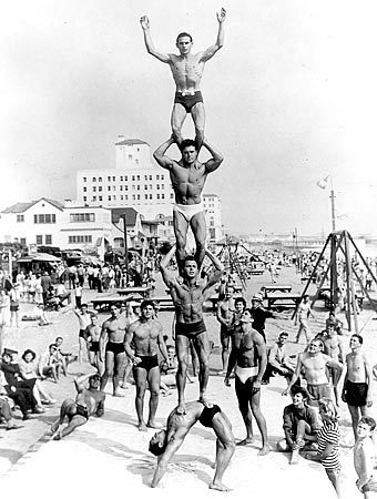 """On the beach in Santa Monica, a young Jack LaLanne is third from the bottom. Harold Zinkin does a back bend, supporting Deforrest """"Moe"""" Most, who supports LaLanne, with Gene Miller on top. LaLanne was the spiritual father of the health movement that blossomed into a national craze of weight rooms, exercise classes and fancy sports clubs."""