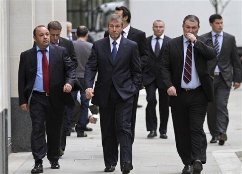 Russian tycoon Roman Abramovich, center, owner of England's Chelsea Football Club, arrives at court in London, Tuesday, Oct. 4, 2011. Self-exiled Russian oligarch Boris Berezovsky has accused Abramovich of betraying and blackmailing him, as the two former business partners face each other in court, in a multibillion dollar lawsuit over an oil deal, where Berezovsky alleges breach of trust and breach of contract by Abramovich in dealings of the Russian oil company Sibneft. (AP Photo/Lefteris Pitarakis)