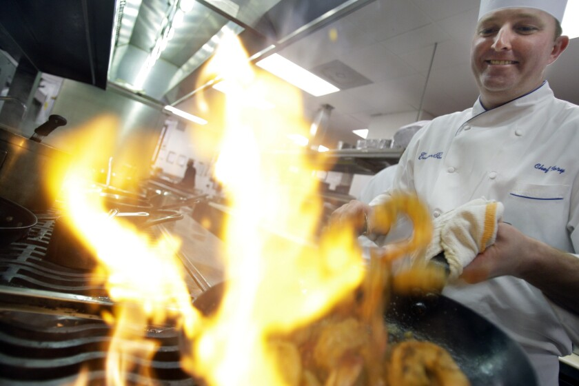 FILE - In this Wednesday, Jan. 7, 2009 file photo, Executive Chef Tory McPhail cooks Lemon and Garlic Crusted Wild Shrimp at Commander's Palace in the Garden District of New Orleans. Tory McPhail, who has been the executive chef at Commander's Palace for 19 years, marked his last day at the legendary restaurant on Thanksgiving, Nov. 26, 2020. He is moving to Bozeman, Montana. (AP Photo/Alex Brandon, File)