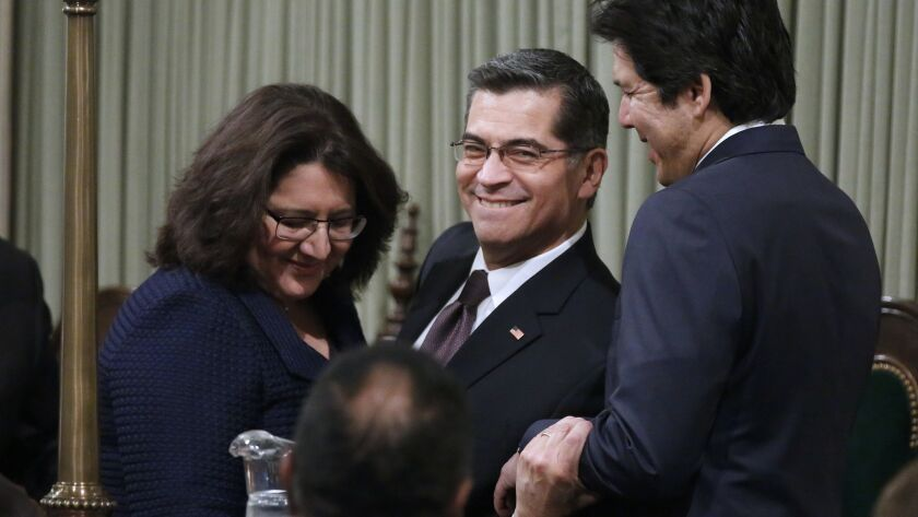 Xavier Becerra, center, and his wife, Carolina Reyes, left, are congratulated by former Senate leader Kevin de León after being sworn in as California's attorney general in 2017.