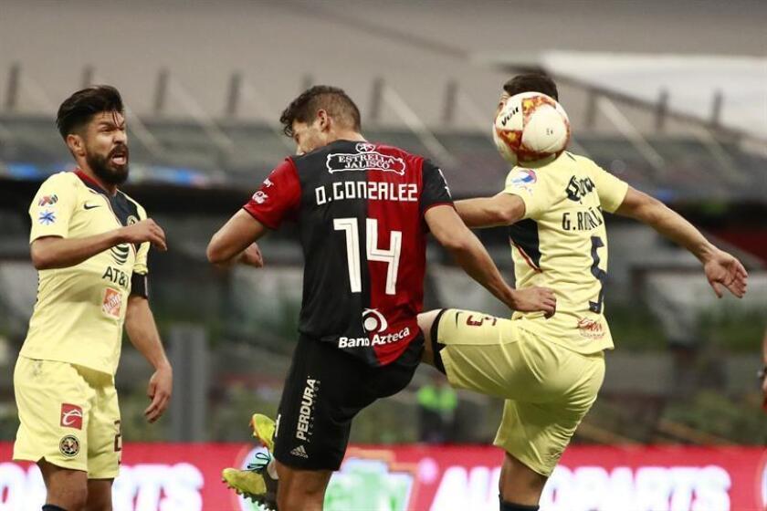 Los jugadores Oribe Peralta (i) y Guido Rodríguez (d) de América disputa el balón con Omar González (c) de Atlas durante el juego. EFE/Archivo