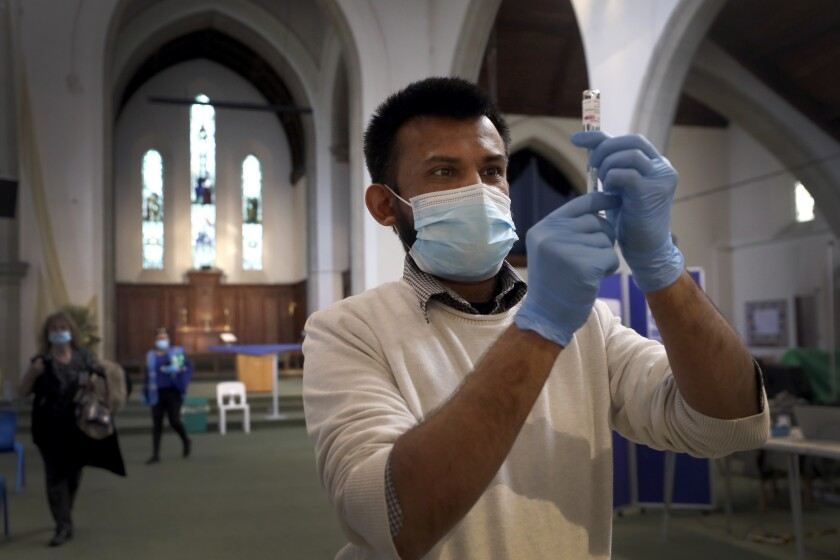 Pharmacist Rajan Shah prepares a syringe of the AstraZeneca vaccine at St John's Church, in Ealing, London, Tuesday, March 16, 2021. In recent days, countries including Denmark, Ireland and Thailand have temporarily suspended their use of AstraZeneca's coronavirus vaccine after reports that some people who got a dose developed blood clots, even though there's no evidence that the shot was responsible. The European Medicines Agency and the World Health Organization say the data available do not suggest the vaccine caused the clots. Britain and several other countries have stuck with the vaccine. (AP Photo/Kirsty Wigglesworth)