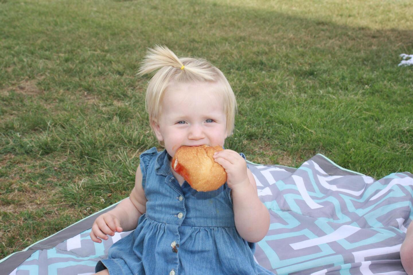 Who needs a burger? Maddie Nowaczyk (1) enjoys a hamburger bun at the annual Bird Rock community picnic Aug. 1, 2017.