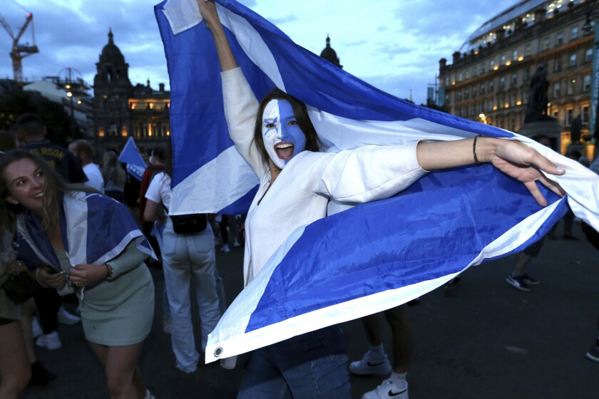 Scotland fans celebrate the Euro 2020 soccer championship group D match between England and Scotland, held at London's Wembley stadium, in Glasgow, Scotland, Friday, June 18, 2021. (Robert Perry/PA via AP)
