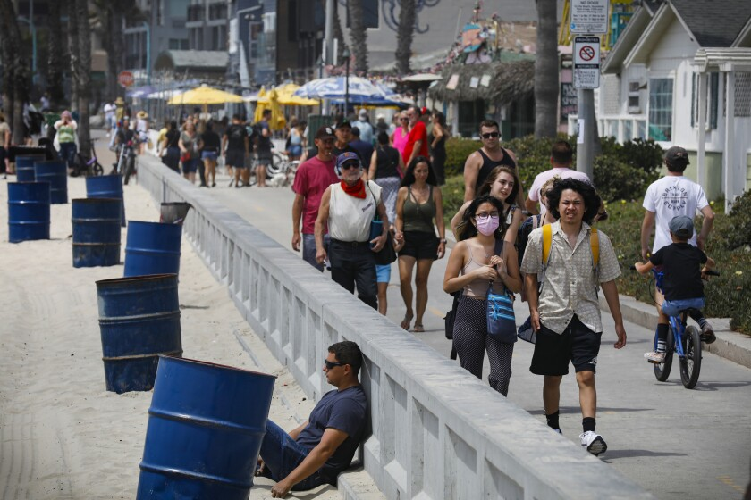 Few people wear masks on the boardwalk in Pacific Beach on Thursday afternoon.