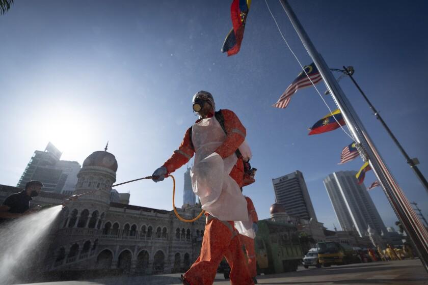 Un operario municipal rocía desinfectante en la Plaza Merdeka, delante del Edificio Sultán Abdul Samad (detrás), en Kuala Lumpur, Malasia, el 17 de octubre de 2020. (AP Foto/Vincent Thian)