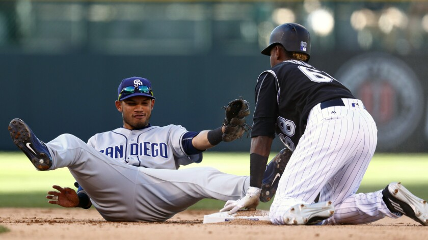 Padres shortstop Luis Sardinas, left, falls back after applying a late tag to Colorado Rockies' Raimel Tapia who stole second base in the seventh inning of a baseball game Sunday, Sept. 18, 2016, in Denver.