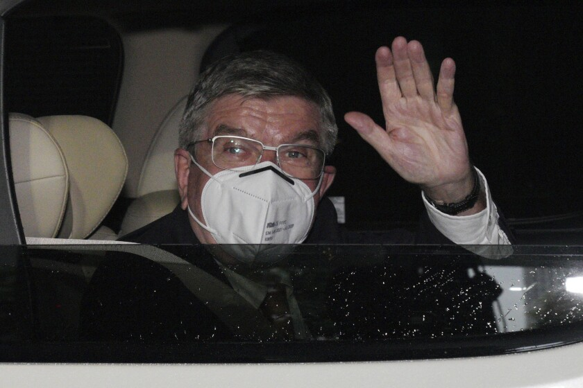 Thomas Bach, wearing a mask, waves from a vehicle.