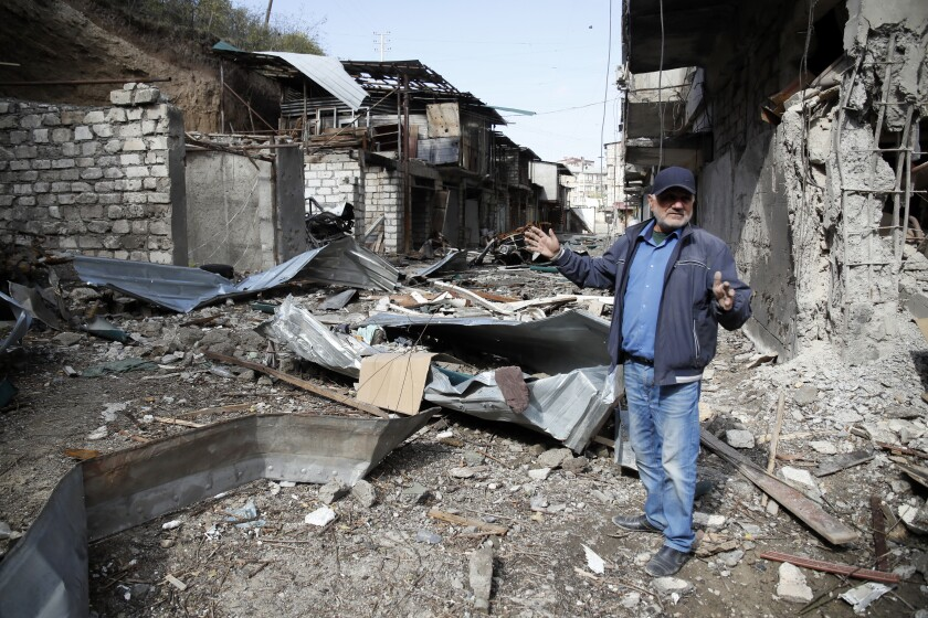 Eduard Chechyan gestures in the yard of his apartment building, destroyed by shelling by Azerbaijan's artillery, during a military conflict in Stepanakert, the separatist region of Nagorno-Karabakh, Saturday, Oct. 10, 2020. Armenia and Azerbaijan have agreed to a Russia-brokered cease-fire in Nagorno-Karabakh after two weeks of heavy fighting that marked the worst outbreak of hostilities in the separatist region in more than a quarter-century. (AP Photo)