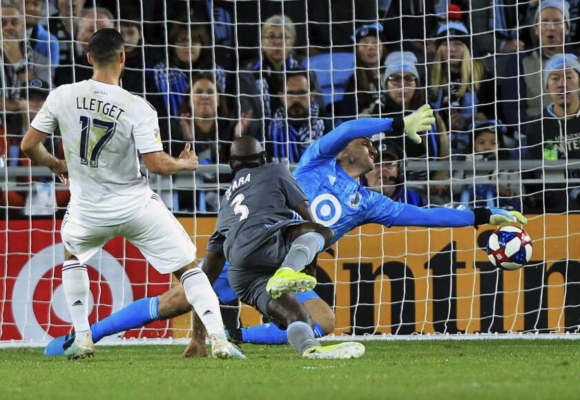 Galaxy midfielder Sebastian Lletget scores past Minnesota United defender Ike Opara and goalie Vito Mannone.