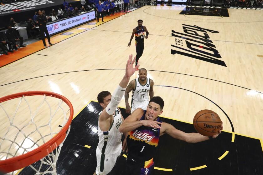El base de los Suns de Phoenix Devin Booker (1) intenta encestar ante el pivote Brook Lopez