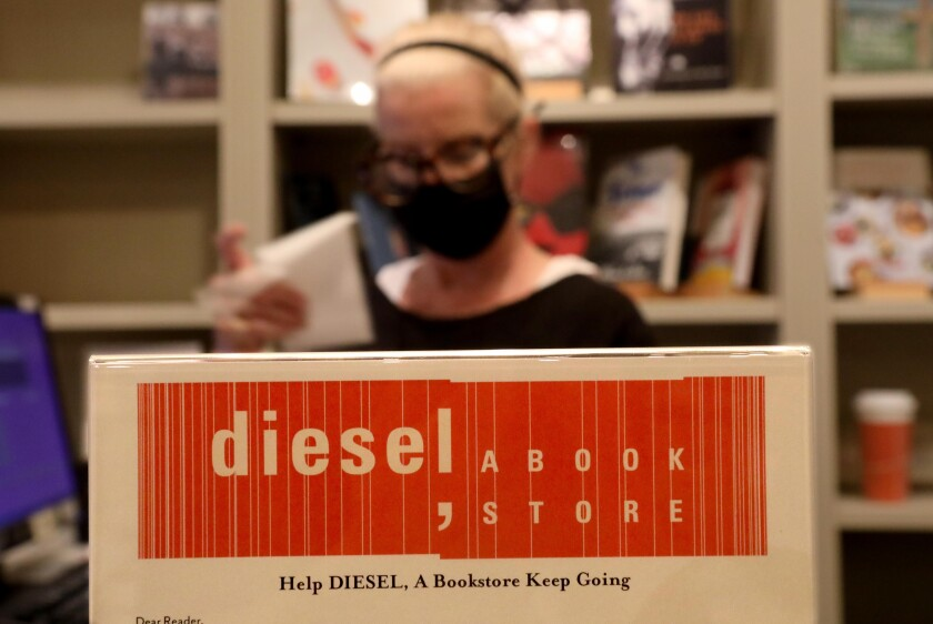 Diesel bookseller Lynn Aime makes a sale next to a sign asking customers to contribute to the shop's GoFundMe.