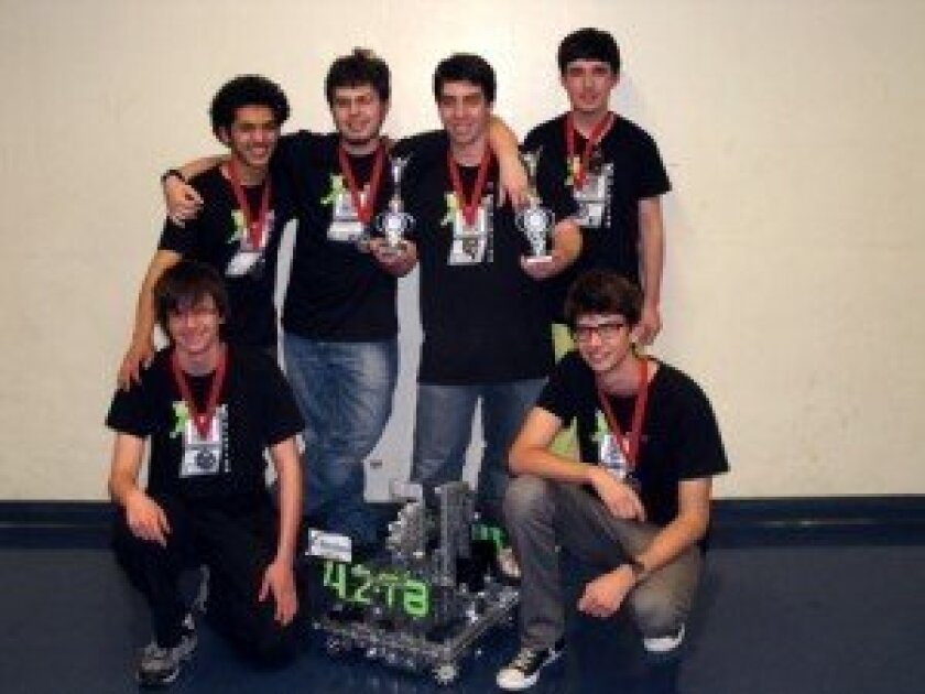 Posing with their winning robot and two trophies are De-Evolution members Noah Sutton-Smolin and Nic Stone (kneeling), and standing are: Yousuf Soliman, Colin Murphy, Tristan Murphy, Ryan Lee. Not pictured: Merry Hodgman.