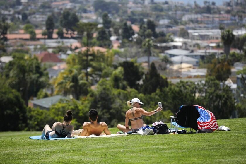 San Diegans lie in the sun at Kate Sessions Park in Pacific Beach in April 2020.