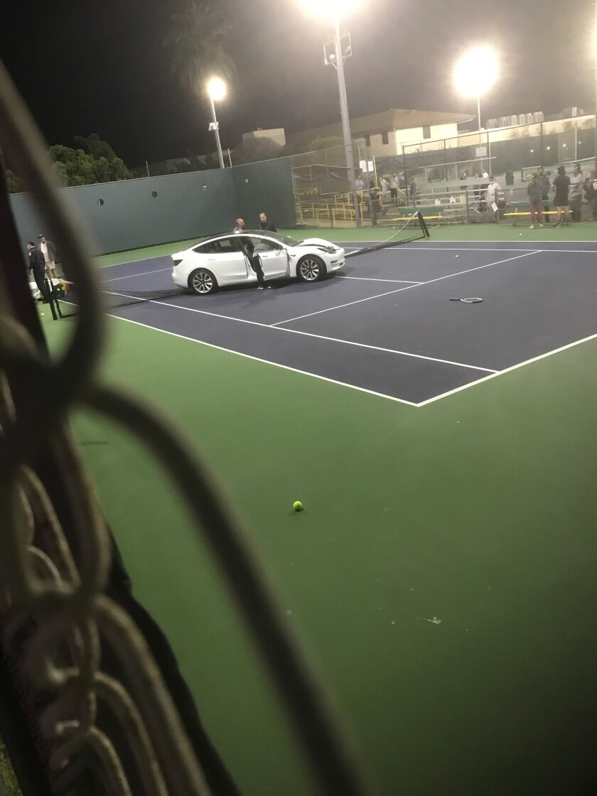 A car sits on a La Jolla Tennis Club court after crashing through the fence the evening of March 2.