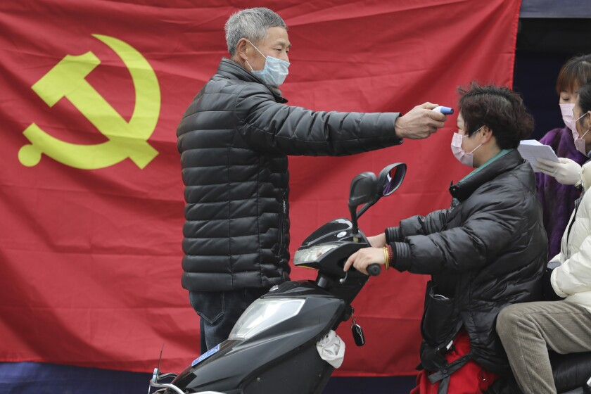 A volunteer takes the temperature of a scooter driver in Hangzhou, China.