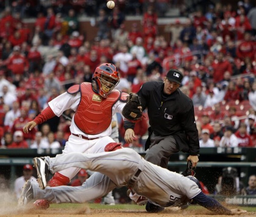 Chase Headley scores the game-winning run as the ball gets away from St. Louis Cardinals catcher Yadier Molina.