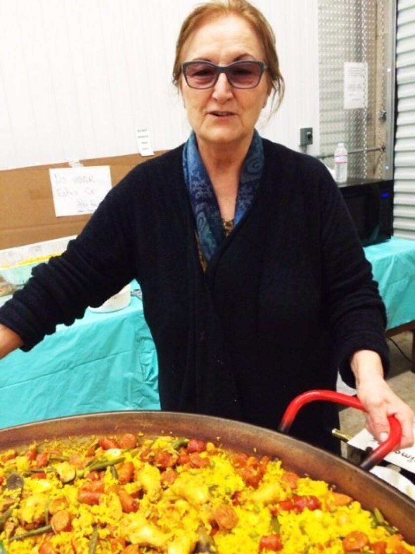 Doña Juana Faraone prepares paella in a giant pan.