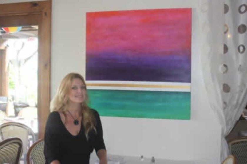 La Jolla artist Kim McBride with one of her paintings at Barbarella Restaurant in La Jolla Shores. Ashley Mackin